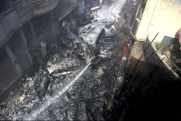 Des pompiers tentent d'éteindre l'incendie causé par le crash, à Karachi.