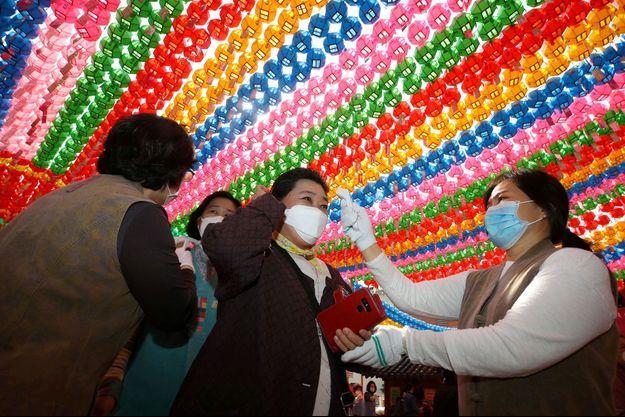 Vérification de la température d'une fidèle dans un temple de Séoul, en Corée du Sud, jeudi.