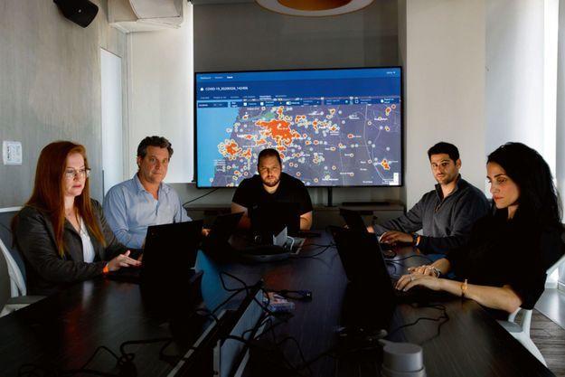 Shalev Hulio, l'un des fondateurs de NSO (au centre), avec ses collaborateurs en août 2020 devant une carte des foyers du Covid. Une de leurs applications permet de les tracer.