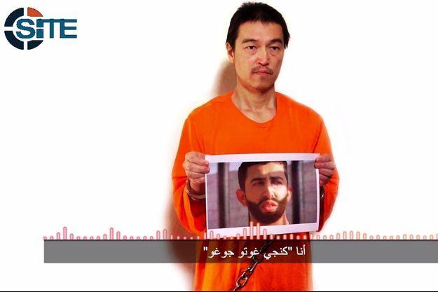 Kenji Goto Jogo brandissant une photo du Jordanien Maaz al-Kassasbeh. Tous deux sont menacés de mort par Daech.
