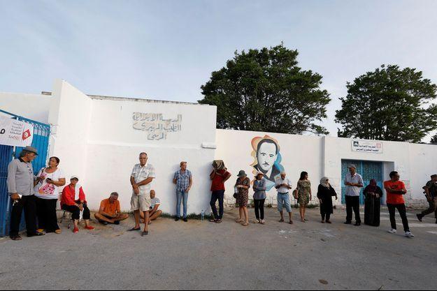 Les Tunisiens en ligne attendent l'ouverture des bureaux de vote.