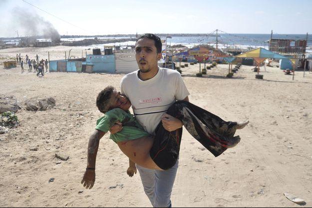 Un homme portant le corps de l'un des quatre enfants tués mercredi sur une plage de Gaza.