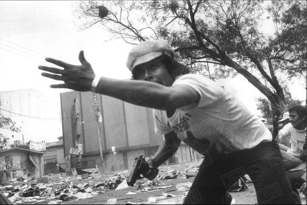 Cet homme, pistolet à la main, en train de courir sur le parvis de la cathédrale de San Salvador, capitale du Salvador, réplique aux tirs d'inconnus qui mitraillent la foule de 350000 personnes venues assister aux obsèques de Mgr Oscar Romero. L'archevêque, grand défenseur des pauvres, dénonçait les exactions commises par l'armée et les escadrons de la mort. Il a été abattu six jours plus tôt, le 24 mars 1980, en pleine messe. Le prélat sera canonisé par le pape François le 14 octobre 2018.