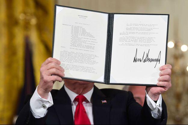 Donald Trump brandit un document relatif à la politique spatiale après l'avoir signé, lundi.