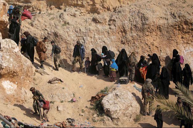 Les combattants de l'État islamique et leurs familles marchent en direction du village de Baghouz, en Syrie, le 12 mars 2019.