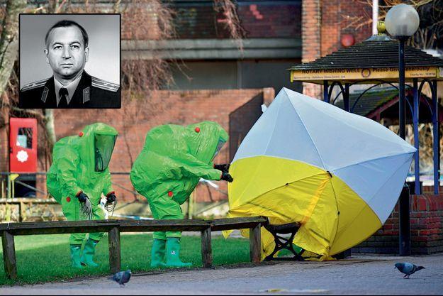 En tenue NRBC (nucléaire, radiologique, biologique et chimique) les pompiers déploient une tente sur le banc où, le 4 mars, ont été retrouvés inanimés Sergueï et Ioulia Skripal. En médaillon: Photo officielle du colonel Sergueï Skripal en uniforme du GRU, les services de renseignement militaire russes.