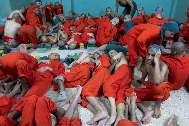 Chacun sa ration d'eau. Pour le reste, ces hommes en combinaison orange, comme à Guantanamo, sont entassés sans procès depuis des mois. Dimanche 29 septembre, dans le nord de la Syrie.