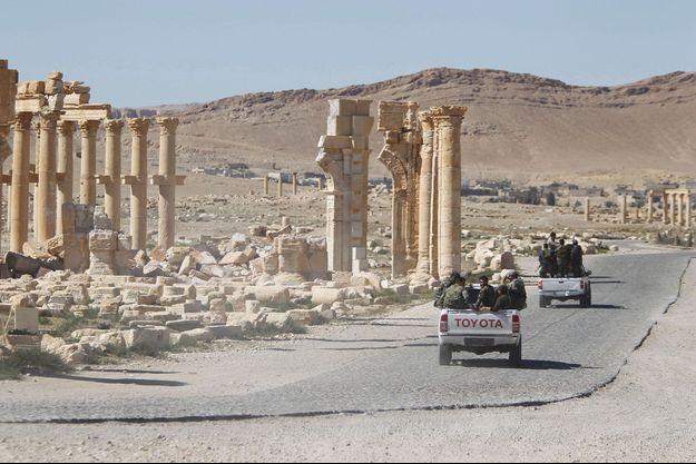 Des véhicules de l'armée syrienne près de l'arc de triomphe de la cité de Palmyre en Syrie