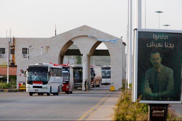 Des réfugiés syriens à bord de bus allant au Liban, en avril 2018.