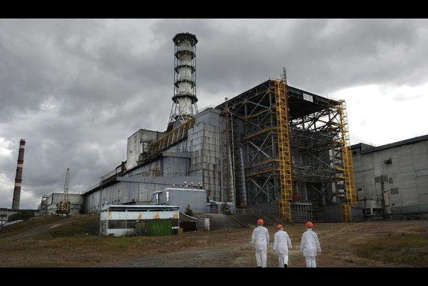 Tchernobyl, 2007. Des ouvriers de dos en combinaison de protection et casque devant le réacteur n°4 entouré de sa structure de stabilisation.