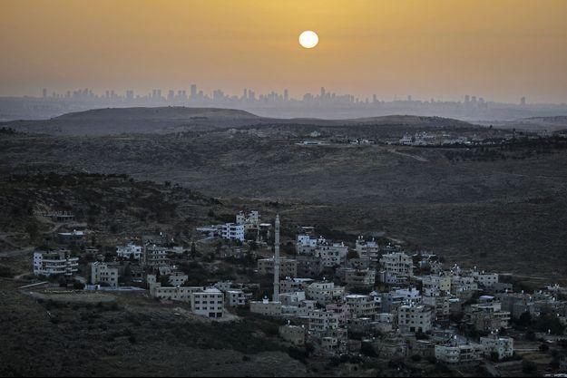 La colonie israélienne de Naale, au nord-ouest de Ramallah, en Cisjordanie, le 17 juin dernier. A l'horizon, les immeubles de Tel Aviv, en Israël.