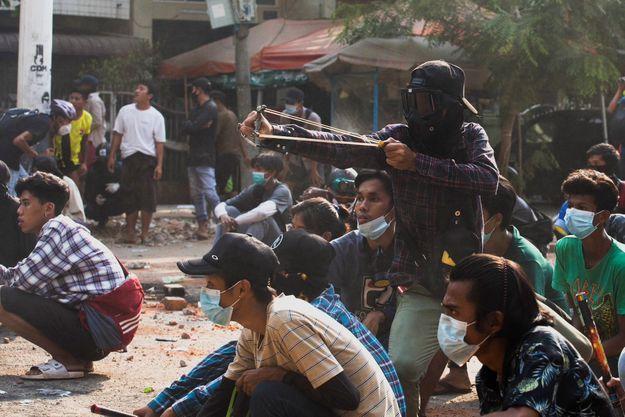 Un homme utilise une fronde lors d'une manifestation contre le coup d'État militaire, à Rangoun en Birmanie, le 28 mars 2021.