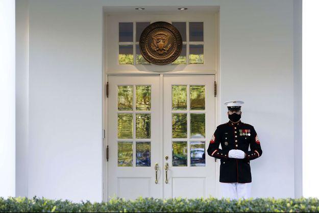 Un Marine masqué monte la garde devant le bureau ovale, à la Maison-Blanche, jeudi, pendant que le président Donald Trump s'y trouve.