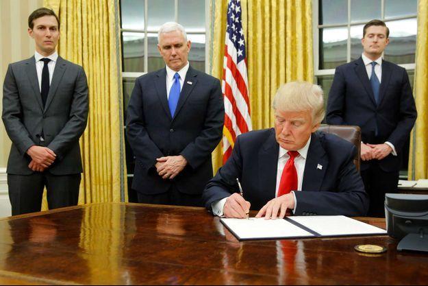 """Donald Trump signe son premier décret, entouré de son conseiller Jared Kushner, du vice-président Mike Pence et du """"staff secretary"""" Rob Porter, en charge des documents qui intéressent le président."""