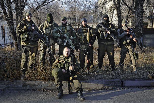 """Un commandant (assis), surnommé """"Serb"""", 23 ans, et sa section Roussich devant leur QG à Lougansk, dimanche 16 novembre. Ils disent avoir pris leurs armes à l'ennemi."""