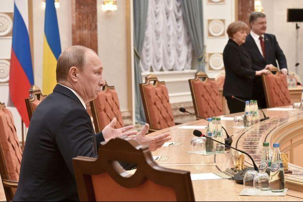 Vladimir Poutine à Minsk, mercredi. Derrière, le président ukrainien Petro Porochenko et la chancelière allemande Angela Merkel.