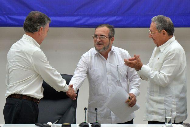 """Sous le regard de Raul Castro (à droite), le président colombien Santos serre la main de Timoleon Jimenez, alias """"Timochenko"""", le chef des Farc"""