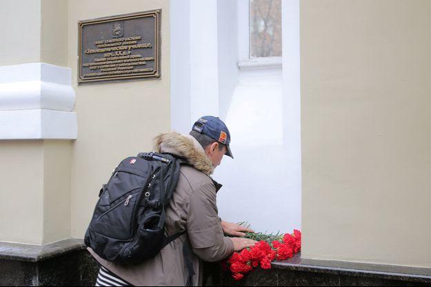 Un homme dépose des fleurs devant l'immeuble qui accueille les choeurs de l'Armée Rouge.