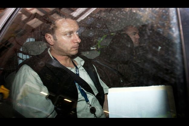 Un policier escorte un suspect lors de son transfert au tribunal.