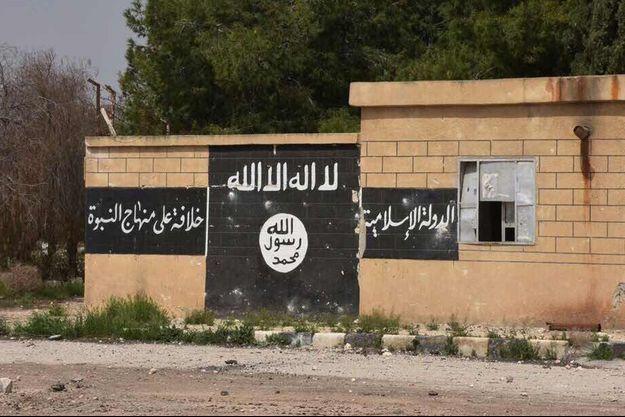 Drapeau du groupe terroriste Etat islamique peint sur un mur.