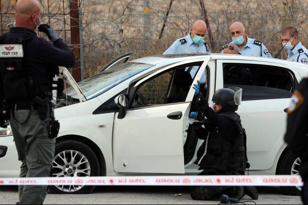 Des policiers israéliens autour du véhicule d'un Palestinien soupçonné d'avoir mené une attaque à la voiture-bélier.