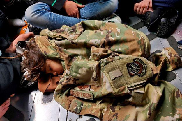 Un petit Afghan se réchauffe avec la veste d'un soldat américain.