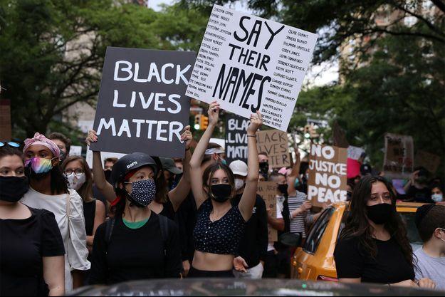 Des manifestantes portent des panneaux sur lesquels sont écrits les noms de victimes noires.
