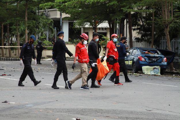 Le personnel de la Croix-Rouge indonésienne porte un sac mortuaire à la suite d'une explosion devant l'église de Makassar, le 28 mars 2021.