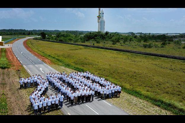 Lundi 14 février, sur la base de Kourou, à 11 h 15 heure locale, 200 salariés d'Arianespace forment le chiffre anniversaire. Au premier rang, au centre : Jean-Yves Le Gall, entouré de son état-major. A l'arrière-plan, le lanceur Ariane 5 en cours de déplacement vers la rampe de lancement.