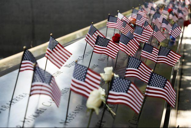 Des drapeaux et des fleurs déposés sur le Mémorial du 11-Septembre, à New York.