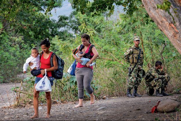 Les militaires colombiens, censés retenir les migrants vénézuéliens sans papiers, laissent passer deux femmes et leurs enfants, qui viennent de franchir le fleuve Tachira.