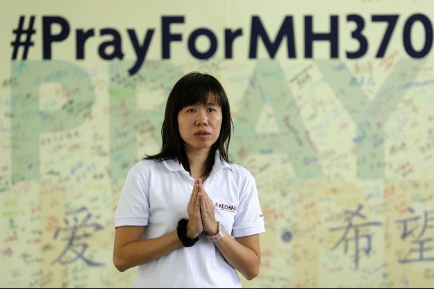 Une femme prie pour les passagers du vol MH370.