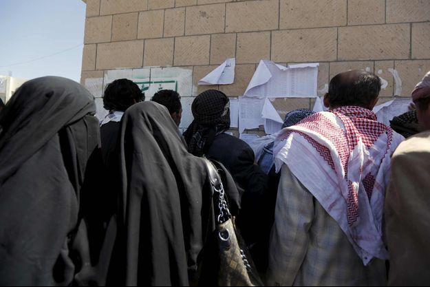 Des Yéménites cherchent leur nom sur les listes donnant droit à de l'aide alimentaire à Sanaa.
