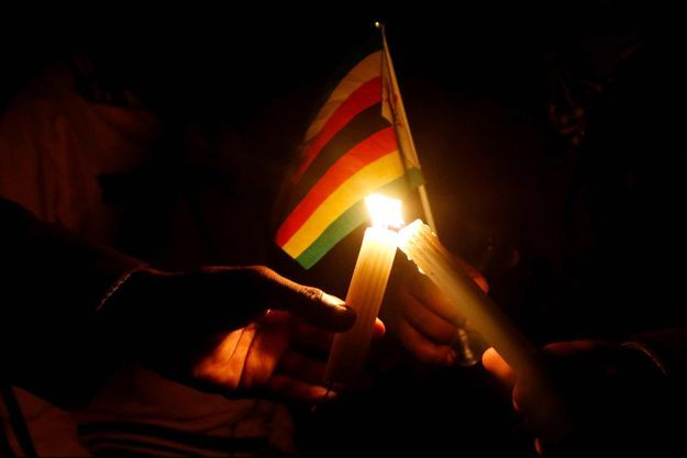 Des partisans du pasteur Evan Mawarire allumant des bougies après sa libération à Harare le 13 juillet.