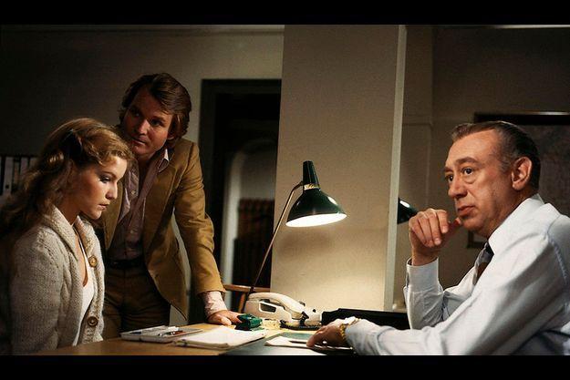 Horst Tapper, alias Stefan Derrick, interroge une jeune femme dans son bureau au décor austère.