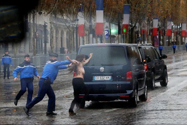 Ici une Femen qui est parvenu à forcer brièvement le dispositif de sécurité au moment où la voiture de Trump descendait les Champs-Elysées.
