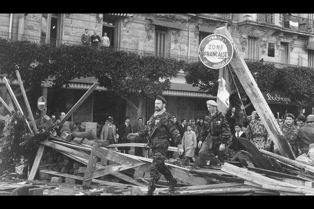 C'est en arme et revêtu de son treillis de para que le député Lagaillarde se rend en franchissant les barricades de la rue Charles-Péguy à Alger.