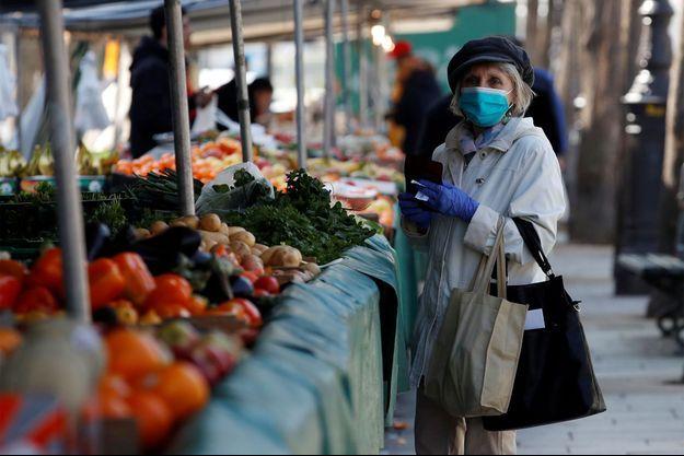 Une femme portant un masque, fait son marché à Bastille, le 24 mars dernier.
