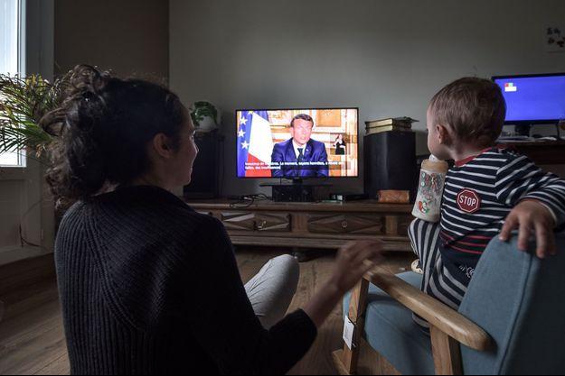 Image d'illustration. Une mère et son enfant à Pau regardant l'allocution présidentielle.