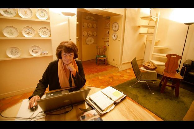Ordinateur portable, agenda bien rempli et un exemplaire de son livre sur cette table où elle travaille.