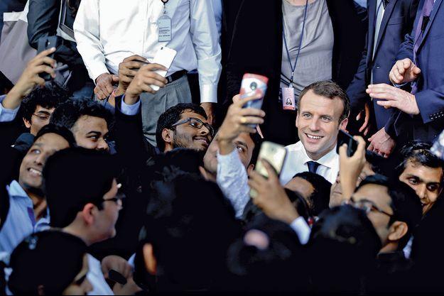 Emmanuel Macron se prête à une séance de selfies avec des étudiants de grandes écoles rencontrés à la Bikaner House à New Delhi, le 10 mars.