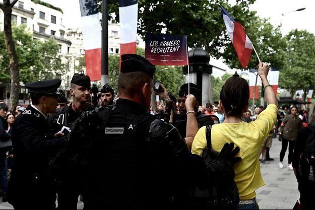 Une femme en jaune, appartenant au mouvement des Gilets jaunes, est entourée par les forces de l'ordre alors qu'elle interpelle Emmanuel Macron lors de son examen des troupes sur les Champs-Élysées.