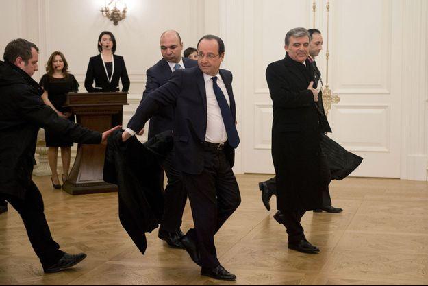 François Hollande confie sa veste à son garde du corps, lundi soir, avant un dîner d'Etat avec le président turc Abdullah Gül.