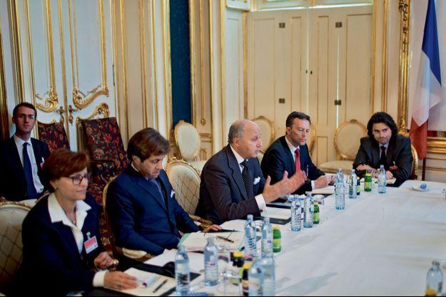 Laurent Fabius entouré de son équipe, pendant une réunion bilatérale entre les représentants français et iraniens.