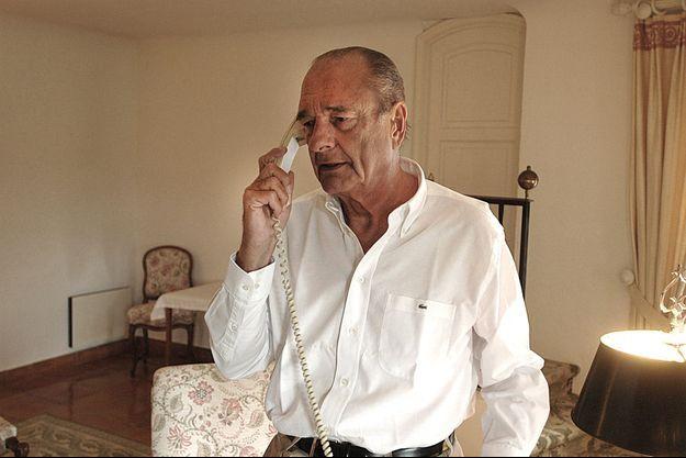 Jacques Chirac, en chemise Lacoste, col ouvert, téléphone dans son bureau du fort de Brégançon, résidence d'été des présidents de la République.