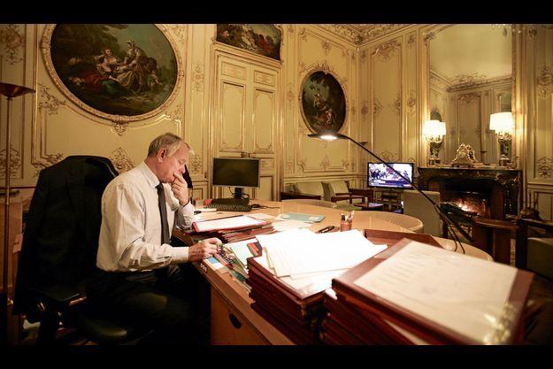 Vendredi 16 novembre, à 20 heures. Une main sur le parapheur, un œil sur le JT, le Premier ministre est encore au travail.