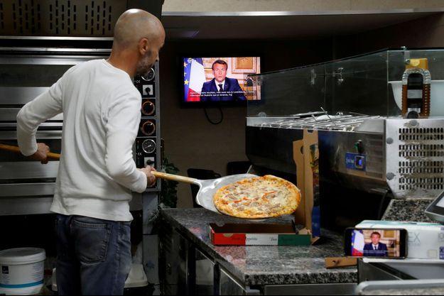 Un pizzaïolo suit l'allocution présidentielle, lundi soir à Nice.