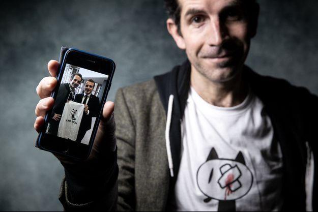 Le dessinateur Jul montrant sa photo avec le chef de l'Etat.