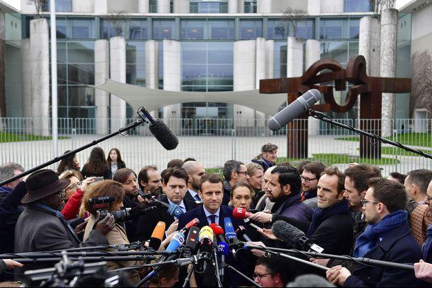 Emmanuel Macron au milieu d'une forêt de micros après sa rencontre avec Angela Merkel, le 16 mars à Berlin.