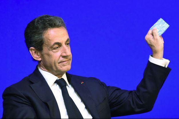 Nicolas Sarkozy brandissant son bulletin de vote.